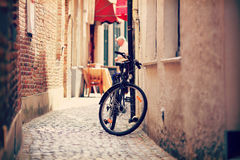 Bycicle on narrow street in Amsterdam. One bycicle on narrow street in Amsterdam. Retro street view of Amsterdam Royalty Free Stock Photo