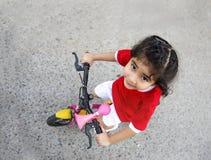 bycicle Reiten des kleinen Mädchens auf der Straße stockfotos