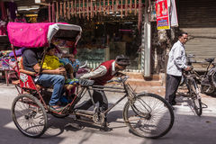 Bycicle riksha. An indian man is pushing his bycicle riksha with three passengers through the market of haridwar, India Stock Image