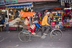 Bycicle riksha. An indian man rides his bycicle riksha with three passengers through the market of haridwar, India Royalty Free Stock Images