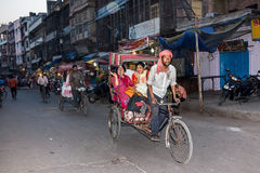 Bycicle riksha. An indian man rides his bycicle riksha with three passengers through the market of haridwar, India Stock Image