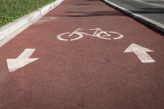 Bycicle symbol on a cycle path. White bycicle symbol on a reddish cycle path Royalty Free Stock Image
