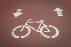 Bycicle symbol on a cycle path. White bycicle symbol on a reddish cycle path Royalty Free Stock Photo
