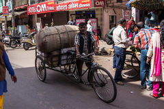 Bycicle transport. An indian man is pushing his bycicle riksha with a heavy load through the market of haridwar, India Royalty Free Stock Photo