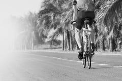 Bycycle biking da estrada da equitação do homem novo na trilha do asfalto no preto a imagens de stock
