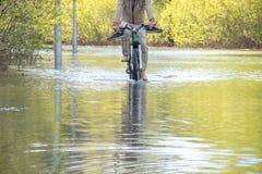 Bycyclist con los pies desnudos intenta superar el agua durante una inundación en primavera Fotografía de archivo