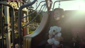 Bycza dziewczyna jedzie na karuzeli i ono uśmiecha się szczęśliwie w parku w jesieni w zwolnionym tempie zdjęcie wideo
