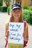 Bye,bye school.Time for holidays. Schoolgirl holding board with written text Bye,bye school.Time for holidays Royalty Free Stock Photo