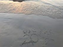 """""""bye tot ziens 2017† op het strand met overzees die wanneer zonsondergang golven stock afbeelding"""