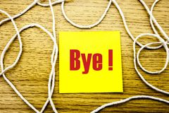 Bye - word on yellow sticky note in wooden background. Bussines concept. Royalty Free Stock Photos
