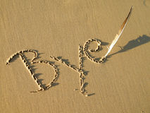 Bye written in sand. The word BYE written in the sand with a bird feather in sunshine Stock Photos