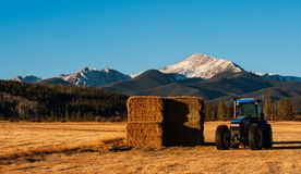 A mountain rises above a tractor and hay field. Byers Peak looms in the background of a blue tractor and a stack of hay in a field Royalty Free Stock Photos