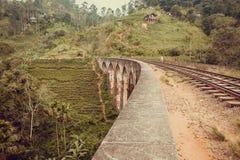 Byfolket går på den gamla bron för nio bågar i härligt tropiskt landskap med den gröna skogen Arkivbild