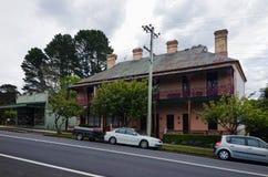 Bygata med gamla historiska hus i blåa berg Aust Arkivfoton