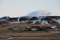 Bygdlandskap i vintern, lokal lantlig lantgård med hus i Island Royaltyfria Bilder