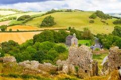 Bygdlandskap med den förstörda slotten, kullar, skogen, ängar och himmel Royaltyfria Bilder