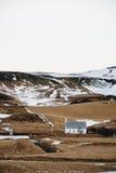 Bygdlandskap, med den lilla kyrkliga ställningen som är ensam på kullar i Island Royaltyfri Bild