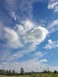 Bygdlandskap och molnig blå himmel Fotografering för Bildbyråer