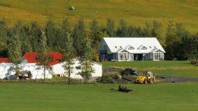 Bygdlandskapet av stora bönder inhyser och lager med den skördade skörden, bilen, traktor
