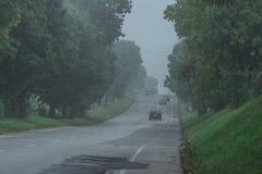 Bygdlutningsväg i dimma Arkivbilder