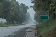 Bygdlutningsväg i dimma med ett vägmärke på vägrenen Royaltyfri Bild