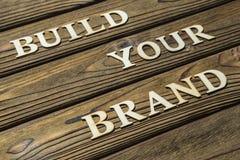 Bygg din märkestext komponeras av bokstäver på en träbakgrund arkivfoton