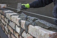 Bygg en tegelstenvägg, mureri som fördelar en sängskarv Royaltyfri Foto