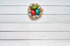 Bygga bo den kulöra äggkransen på vit träplankabakgrund östligt Fotografering för Bildbyråer
