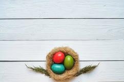 Bygga bo den kulöra äggkransen på vit träplankabakgrund Royaltyfria Foton