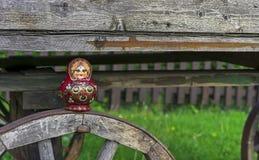 Bygga bo docka på bakgrunden av en gammal trävagn Matryoshka ?r en nationell rysk souvenir royaltyfri fotografi