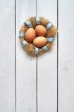 Bygga bo kransen med ägg på lantlig bakgrund för vita träplankor Arkivfoto
