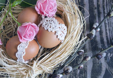 Bygga bo med dekorerat ägg, rosor och pilris på tappningträbakgrund Ordning för våreaster ferie Royaltyfria Foton
