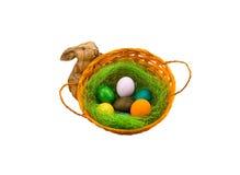 Bygga bo med färgrika ägg i korgen träkaninstatyett på en vit bakgrund Royaltyfria Bilder