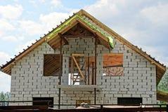 Bygga en vit tegelsten inhysa mot himlen och molnen Royaltyfri Fotografi