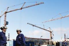 Byggande arbetare, kranar och material till byggnadsställning Royaltyfria Foton