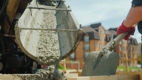 Byggande av en stuga Arbetare tar betong från en blandare in i en träformwork royaltyfria bilder