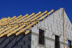 Byggande av ett hus av träplankor och gråa tegelstenar mot en blå himmel arkivfoto
