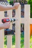 Byggande av ett trästaket med en drillborr och en skruv Slut upp av hans arkivfoto