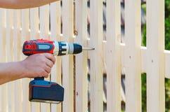 Byggande av ett trästaket med en drillborr och en skruv Stäng sig upp av hans hand och hjälpmedlet i ett DIY-begrepp Royaltyfri Foto