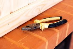byggande drillisolering tools white Plattång och stämjärn på röd tegelsten royaltyfri foto