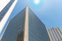 Byggande exponeringsglas för modern affär av skyskrapor med solen Arkivfoton