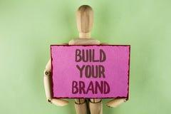 Byggande för handskrifttexthandstil ditt märke Begreppsbetydelsen skapar din egen logosloganmodell som annonserar att marknadsför royaltyfri fotografi