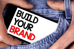 Byggande för handskrifttexthandstil ditt märke Begreppsbetydelsen skapar din egen logosloganmodell som annonserar att marknadsför royaltyfri bild
