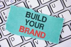 Byggande för handskrifttexthandstil ditt märke Begreppsbetydelsen skapar din egen logosloganmodell som annonserar att marknadsför arkivbild