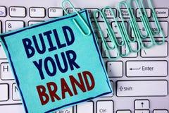 Byggande för ordhandstiltext ditt märke Affärsidéen för skapar din egen logosloganmodell som annonserar att marknadsföra för E so royaltyfri foto