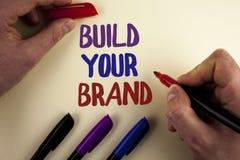 Byggande för textteckenvisning ditt märke Det begreppsmässiga fotoet skapar din egen logosloganmodell som annonserar att marknads royaltyfri bild