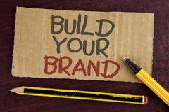Byggande för textteckenvisning ditt märke Det begreppsmässiga fotoet skapar din egen logosloganmodell som annonserar att marknads royaltyfri foto