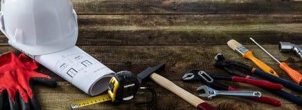 Byggande hjälm och yrkesmässiga maskinvaruhjälpmedel på DIY-träbakgrund royaltyfri bild