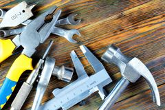 Byggande hjälpmedel på träbakgrund, ferie, faderdag Populära låssmedhjälpmedel för kreativitet och affären - hammaren av royaltyfri foto