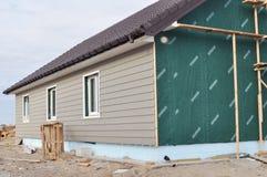 Byggande hus med väggisolering, waterpfoofmembranet, plast- siding-, guttering- och fundamentisolering med polystyren fotografering för bildbyråer